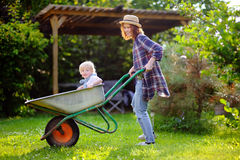 Adorable toddler boy having fun in a wheelbarrow pushing by mum in domestic garden, on warm sunny day Royalty Free Stock Image