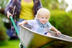 Adorable toddler boy having fun in a wheelbarrow pushing by mum in domestic garden, on warm sunny day Stock Photos