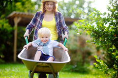 Adorable toddler boy having fun in a wheelbarrow pushing by mum in domestic garden on warm sunny day Stock Image