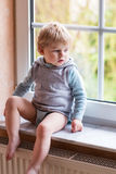 Adorable toddler boy looking out of the window Stock Photos