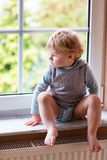 Adorable toddler boy looking out of the window Royalty Free Stock Images