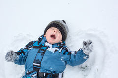 Adorable toddler boy making angel on snow Stock Photo