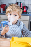 Adorable toddler  boy making inhalation with nebulizer Stock Photos