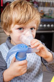 Adorable toddler  boy making inhalation Stock Photo