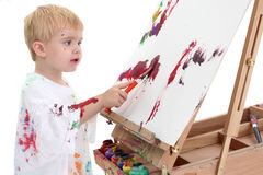 Adorable Toddler Boy Painting at Easel stock photos