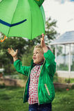 Adorable toddler boy play with green umbrella Royalty Free Stock Photography