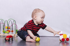 Adorable toddler boy playing with a toy duck on the grey floor royalty free stock photos