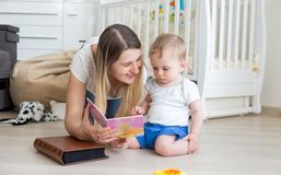 Adorable toddler boy sitting on floor with mother and reading book. Toddler boy sitting on floor with mother and reading book Royalty Free Stock Photos
