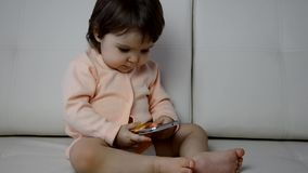 Adorable toddler boy sitting on the sofa in the living room and playing with smartphone. Child learning how to use stock video footage