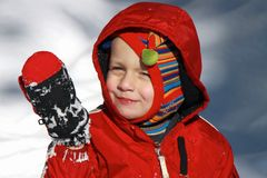 Adorable toddler boy in the snow. Happy blonde boy playing in the snow Royalty Free Stock Images