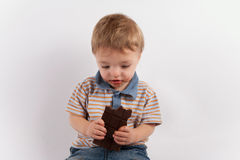 Adorable toddler boy thinking over a chocolate bar Stock Photo