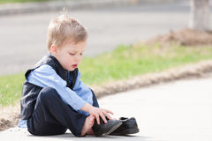 Adorable toddler boy trying to put his shoes on. Adorable toddler boy in suit trying to put his shoes on Royalty Free Stock Images