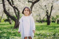 Adorable toddler child girl in light blue dressy outfit walking and playing in blooming spring garden Stock Images
