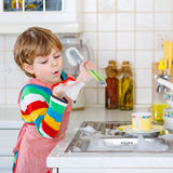 Adorable toddler child washing dishes in domestic kitchen. Royalty Free Stock Image
