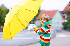 Adorable toddler child with yellow umbrella and colorful jacket Royalty Free Stock Photo