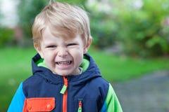 Adorable toddler in colorful autumn jacket Stock Photos