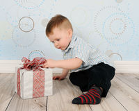 Adorable toddler curious about a christmas present Royalty Free Stock Photos