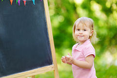 Adorable toddler drawing with a chalk Stock Photo