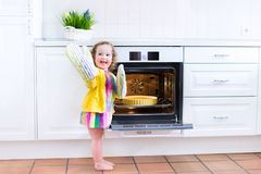 Adorable toddler girl with an apple pie in the oven Royalty Free Stock Image