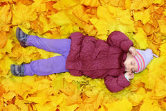 Adorable toddler girl with autumn leaves. Adorable toddler girl sleeping in autumn leaves Stock Images