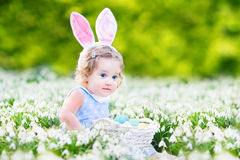Adorable toddler girl in bunny ears wiht first spring flow Stock Photos