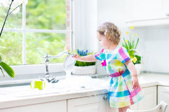 Adorable toddler girl in colorful dress washing dishes. Cute curly toddler girl in a colorful dress washing dishes, cleaning with a sponge and playing with foam stock photography