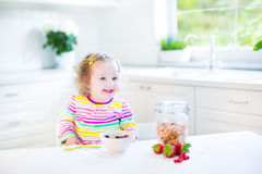 Adorable toddler girl with curly hair having breakfast. Beautiful toddler girl with curly hair wearing a colorful shirt having breakfast drinking juice in a Royalty Free Stock Photos