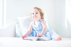 Adorable toddler girl with curly hair reading a book Stock Photography