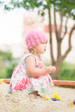 Adorable toddler girl in dress play on sandbox Royalty Free Stock Photo