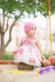 Adorable toddler girl in dress play on sandbox Royalty Free Stock Photos