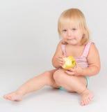 Adorable toddler girl eat green fresh apple Stock Photo