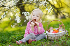 Adorable toddler girl eating chocolate bunny. In a spring garden on Easter day Stock Images