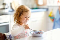 Adorable toddler girl eating healthy cereal with milk for breakfast. Cute happy baby child in colorful clothes sitting stock photography