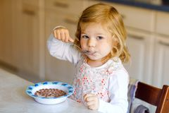 Adorable toddler girl eating healthy cereal with milk for breakfast. Cute happy baby child in colorful clothes sitting stock images