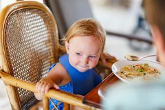 Toddler girl eating lunch. Adorable toddler girl eating healthy lunch stock images