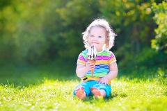 Adorable toddler girl eating ice cream in a garden Stock Image