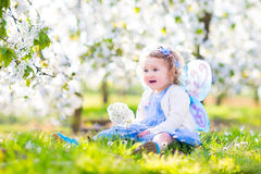 Adorable toddler girl in fairy costume in fruit garden. Adorable toddler girl with curly hair and flower crown wearing a magic fairy costume with a blue dress Royalty Free Stock Photography