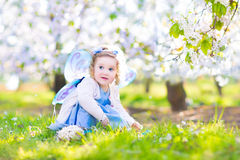 Adorable toddler girl in fairy costume in fruit garden royalty free stock image