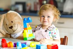 Adorable toddler girl with favorite plush bunny playing with educational toys in nursery. Happy healthy child having fun. With colorful different plastic blocks royalty free stock images