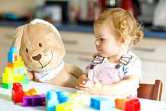Adorable toddler girl with favorite plush bunny playing with educational toys in nursery. Happy healthy child having fun. With colorful different plastic blocks stock photography