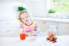 Adorable toddler girl having breakfast drinking juice. Beautiful toddler girl with curly hair wearing a colorful shirt having breakfast drinking juice in a white Royalty Free Stock Photography