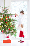 Adorable toddler girl helping her brother to decorate a beautiful Christmas tree. Adorable toddler girl with curly hair wearing a warm red dress helping her Royalty Free Stock Photo