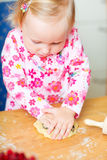 Adorable toddler girl helping at kitchen Stock Images