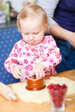 Adorable toddler girl helping at kitchen Royalty Free Stock Photo