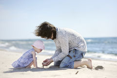 Adorable toddler girl and her father on a beach Stock Photos