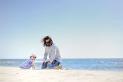 Adorable toddler girl and her father on a beach Royalty Free Stock Image
