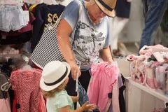 Cute little girl and her grandmother choosing clothes in the shop. Royalty Free Stock Photos
