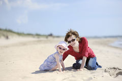 Adorable toddler girl and her mother on a beach Stock Photos