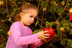 Adorable toddler girl holding decorative Christmas toy ball Stock Photos