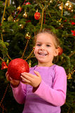 Adorable toddler girl holding decorative Christmas toy ball Stock Photo